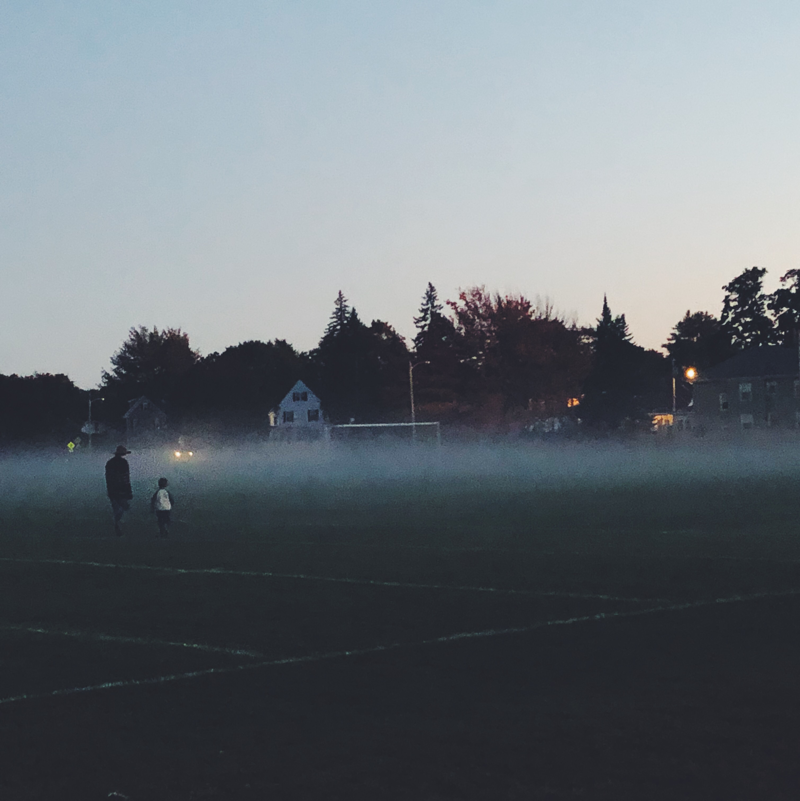 A child and parent run across a misty field at dusk.