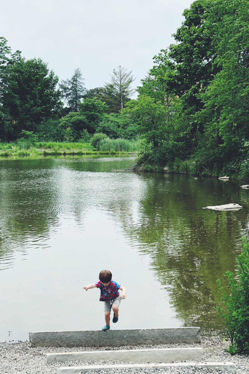 A child in tie dye plays by a large pond.