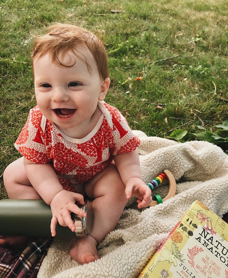 A baby laughing, sitting on grass.