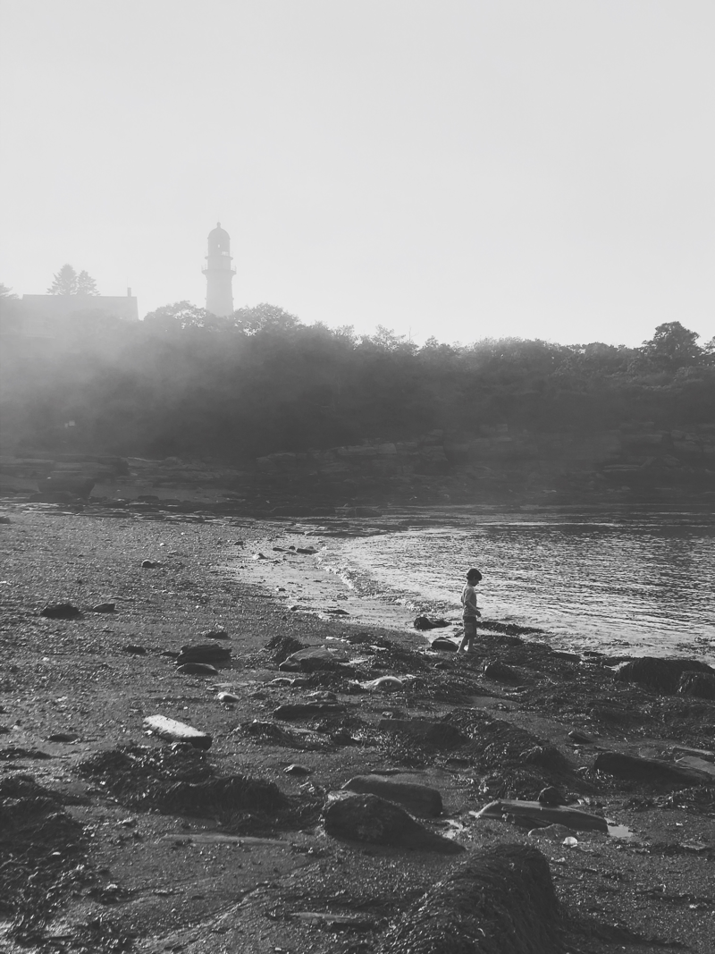 A child plays in the fog at a beach by a light house during sunset.