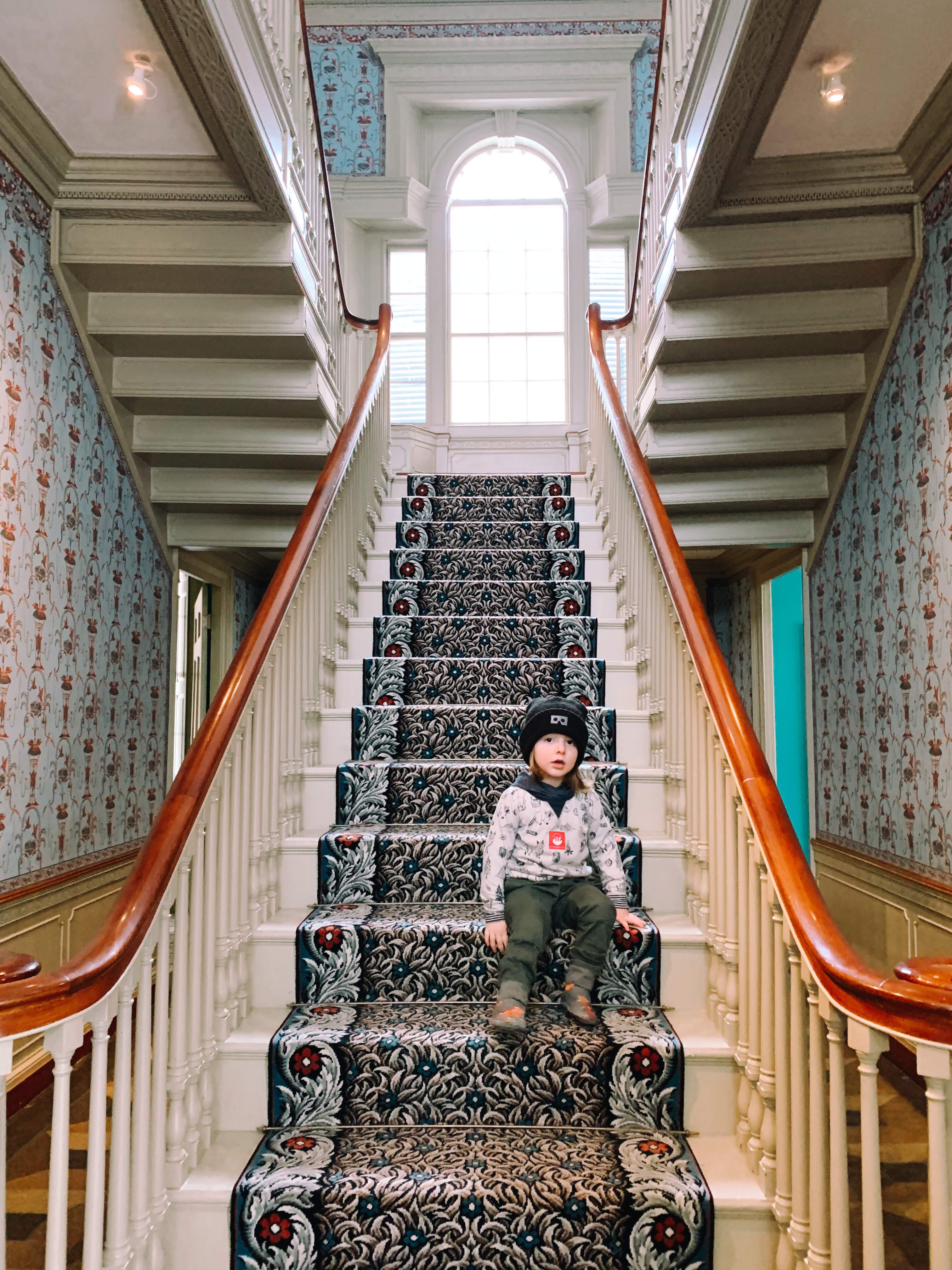 A 3 year old wearing a black beanie sitting on an elaborately carpeted staircase.