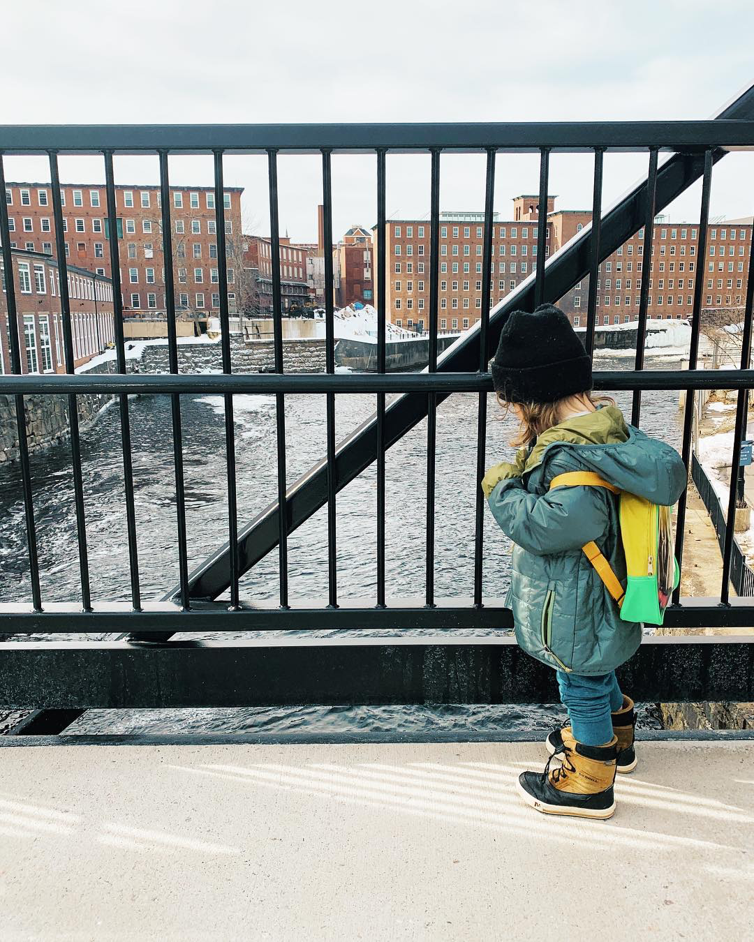 Child in a winter coat and a black hat wearing a yellow backpack standing on a bridge overlooking a river and some brick mills.