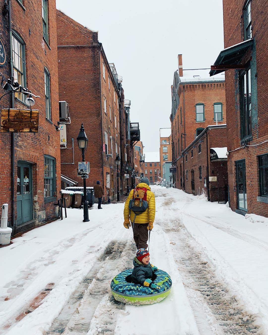 Man in yellow coat pulling a child on a sled through a snowy city street.