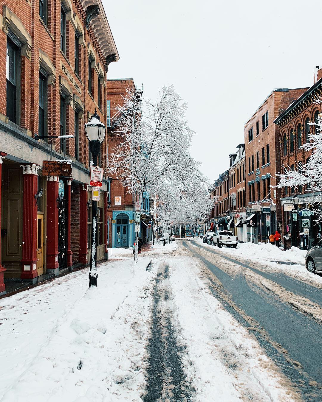 A snowy street, with brick buildings along either side.