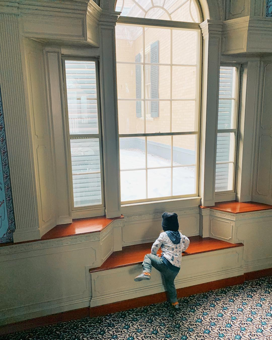 Child climbing into an ornate window seat.