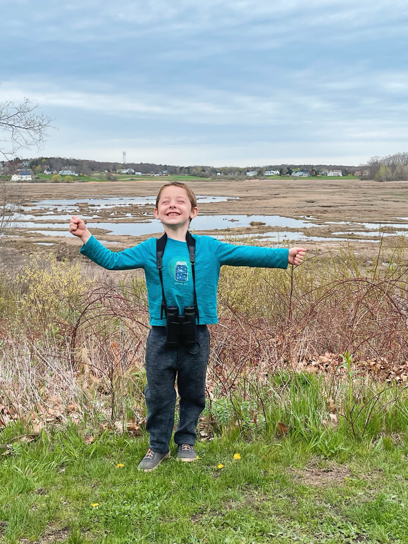 A happy child wearing a pair of binoculars standing at a marsh.