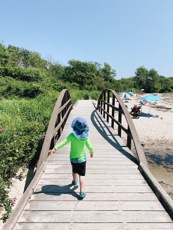 A child wearing lots of sun protection strolling on a boardwalk by a Maine-coast beach.
