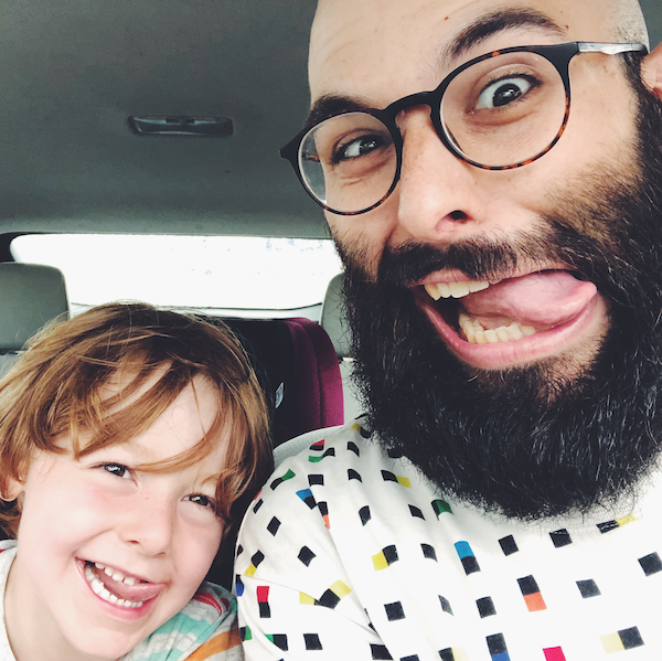 Red headed kid, and bearded bald man with glasses make funny faces in a car.