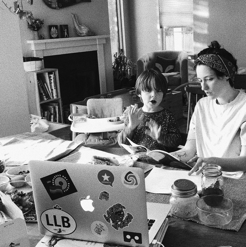 A mother and child sit together at a table with a computer in front of them sharing a meal.