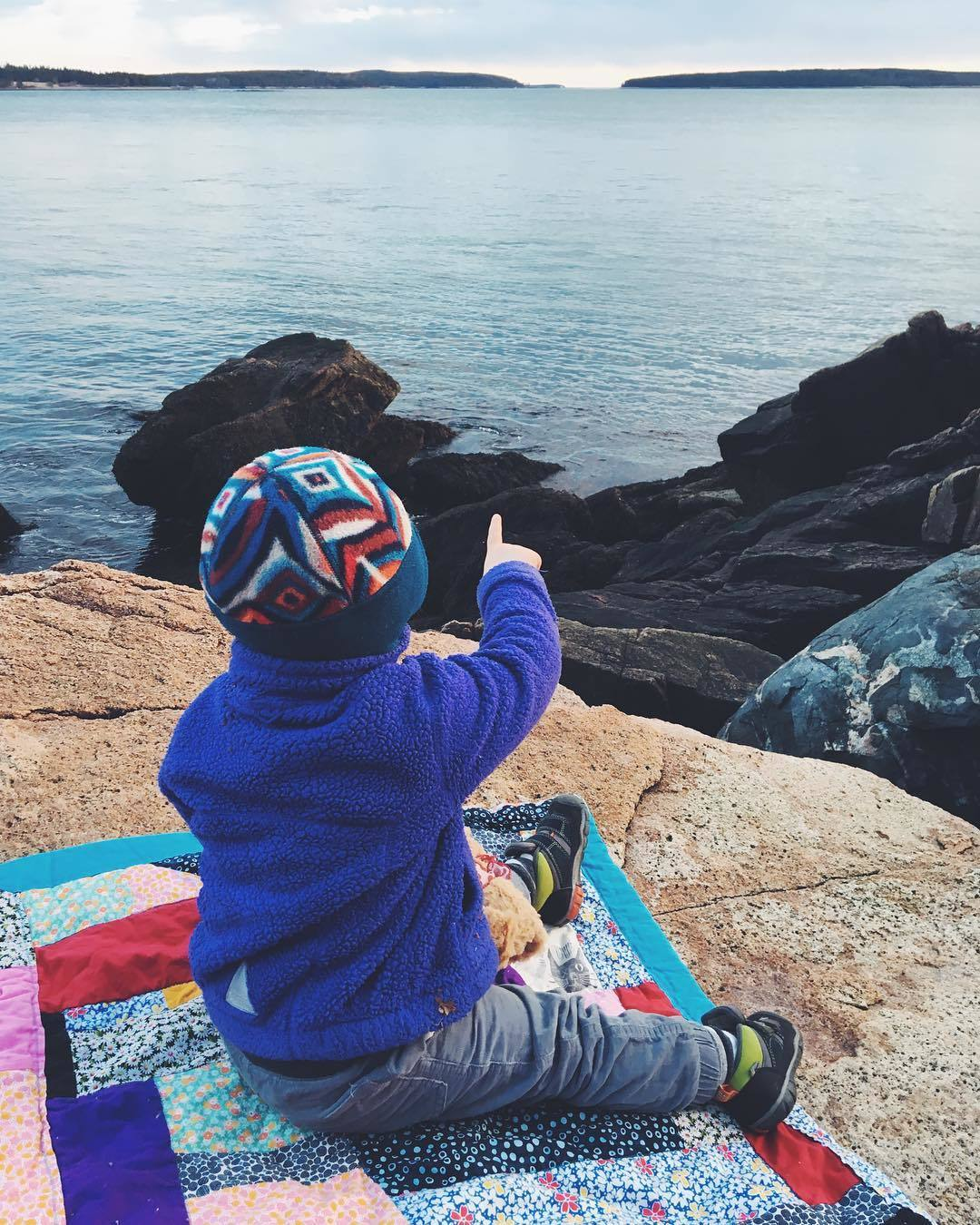 A young child in warm clothes sits on a rock, while pointing at the ocean.