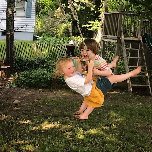 Two kids on a rope swing.