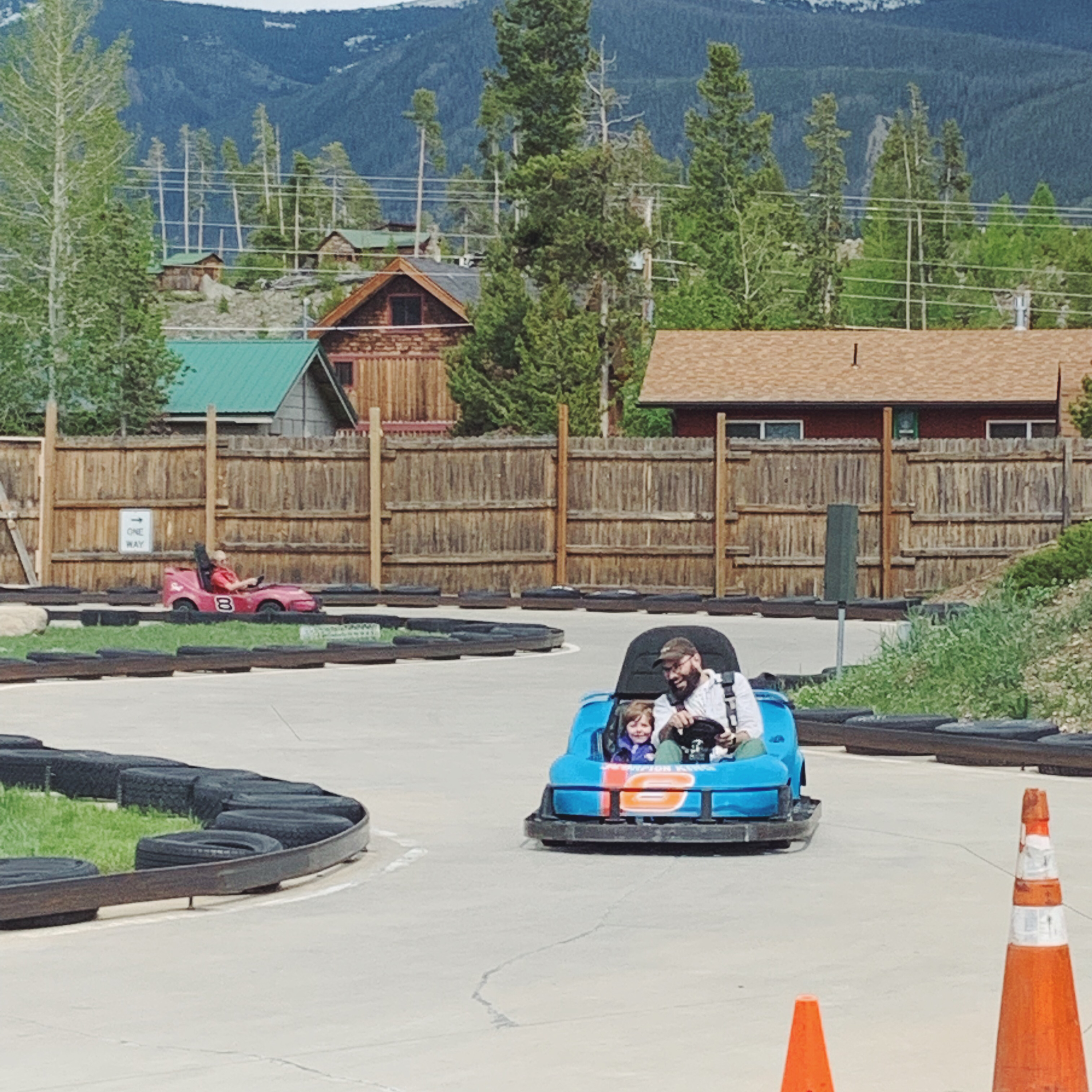 A father and son in a blue go kart.